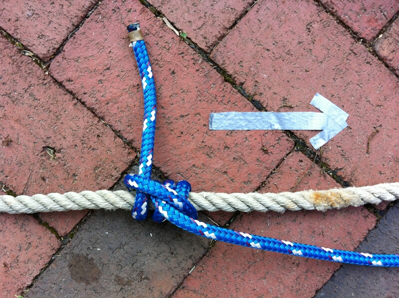 This rolling hitch has an extra round turn at the bottom because the braid is slippery. The hitch needs to lie very close to the line it's pulling, and be cinched up tightly. The duct-tape arrow shows the direction of pull.