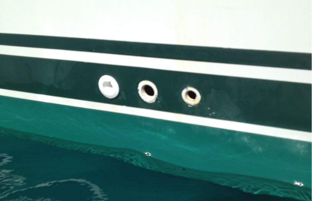 Years of UV exposure weakened two of these three plastic drain fittings. The outboard flanges dropped off and the hoses fell inside the boat, leaving potential boat-sinking holes just above the waterline.  Doug Logan photo.