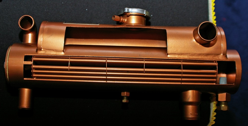 A cutaway view of this heat exchanger shows cooling tubes, expansion tank, pressure cap, and sacrificial zinc anode on the lower right.